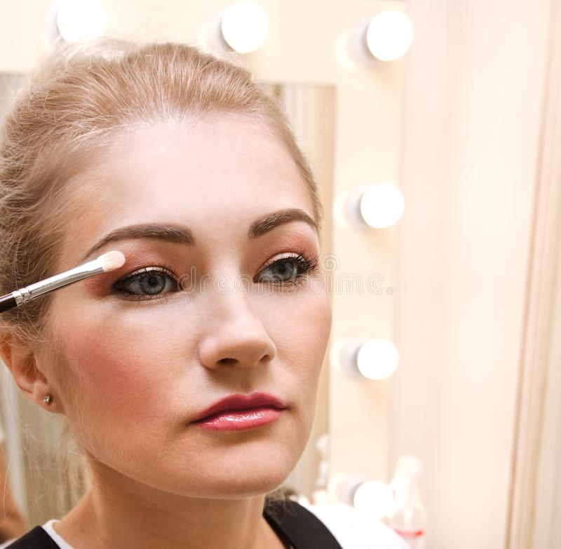 Process av danandemakeup Härlig ung kvinna som applicerar ögonskugga Hand med borsten på modellframsida royaltyfri fotografi