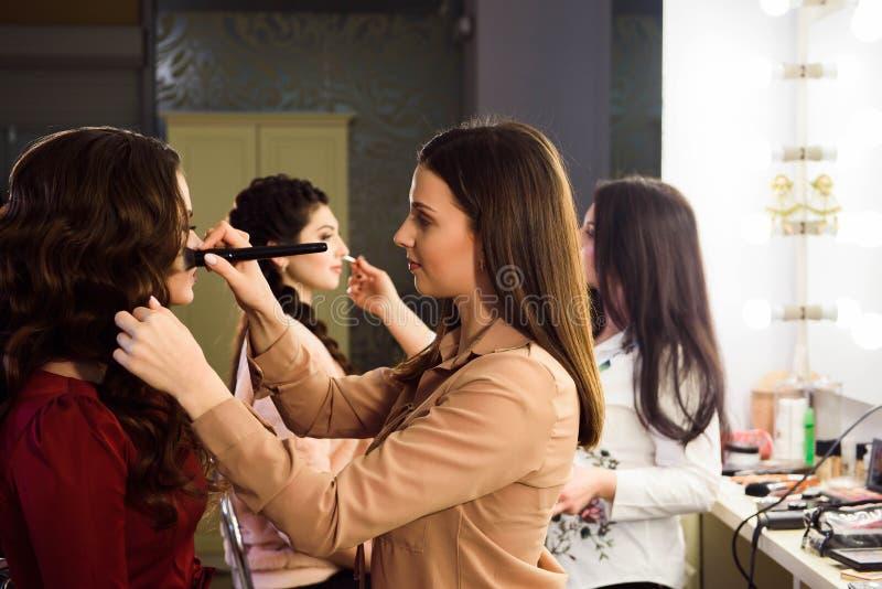 Process av danandemakeup Sminkkonstnär som arbetar med borsten på modellframsida Stående av den unga kvinnan i skönhetsalong royaltyfria foton