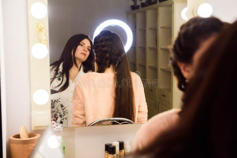 Process av danandemakeup Sminkkonstnär som arbetar med borsten på modellframsida Stående av den unga kvinnan i skönhetsalong arkivbilder