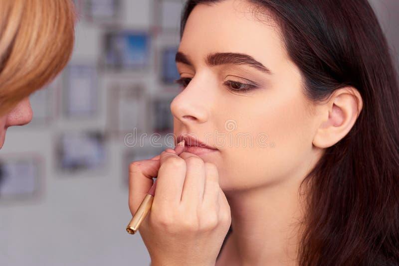 Process av danandemakeup Sminkkonstnär som arbetar med borsten på modellframsida Stående av den unga kvinnan i skönhetsalonginre arkivfoto