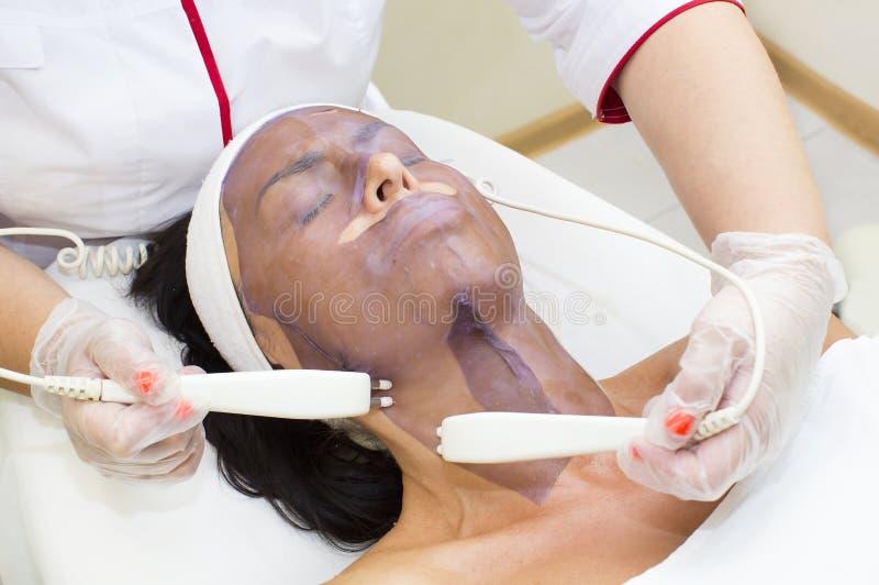 Process av massagen och ansiktsbehandlingar arkivbilder
