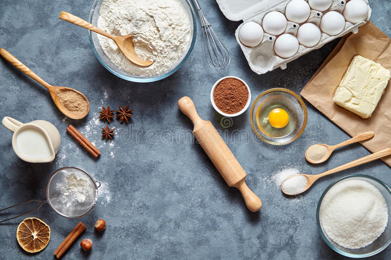 The process Baking cake in kitchen - dough recipe ingredients eggs, flour, milk, butter, sugar on table from above. royalty free stock image