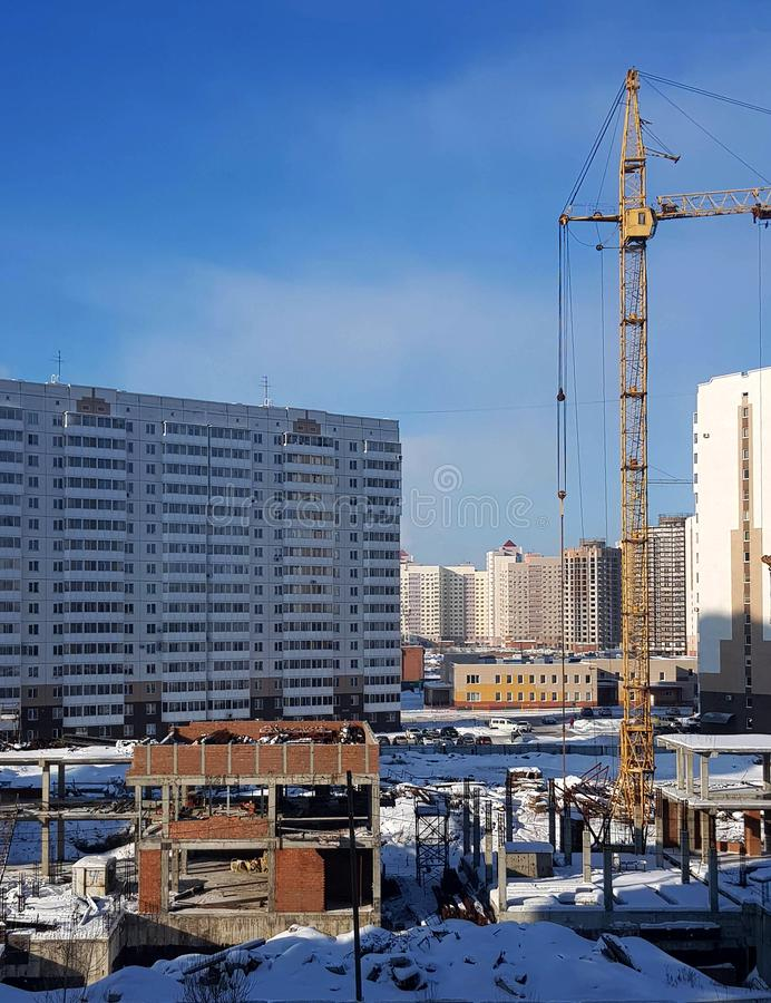 The process of building new high-rise buildings, tower cranes and block structures against a blue sky. Modern apartment buildings stock image