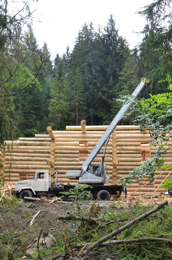 The process of building a wooden house from wooden beams of cylindrical shape. Crane in working condition royalty free stock photo