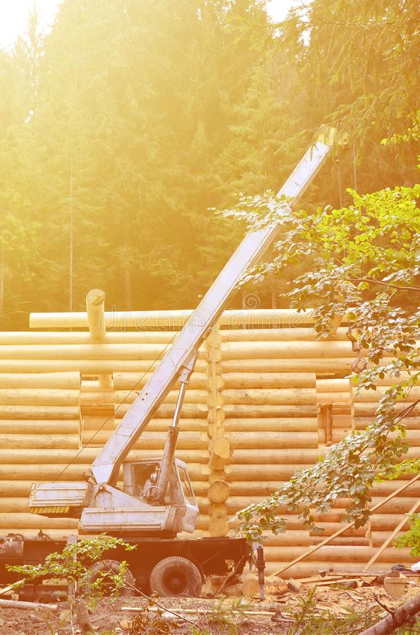 The process of building a wooden house from wooden beams of cylindrical shape. Crane in working condition stock images
