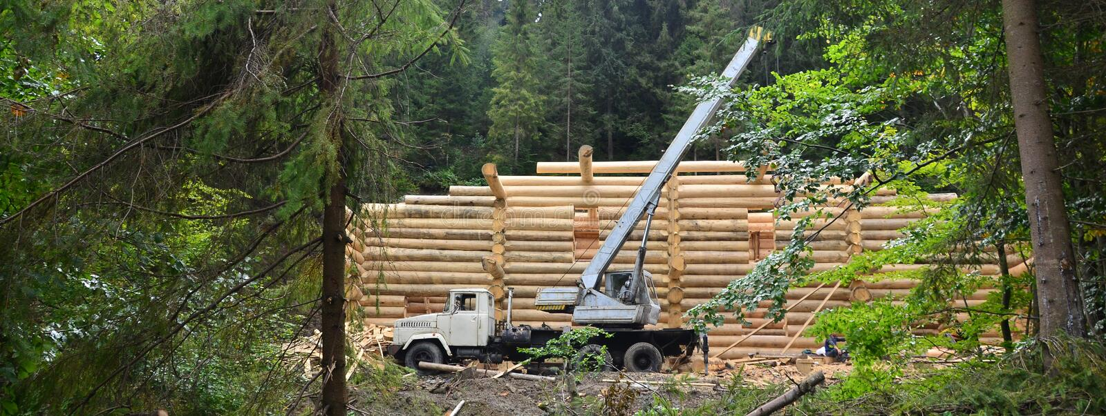 The process of building a wooden house from wooden beams of cylindrical shape. Crane in working condition royalty free stock image