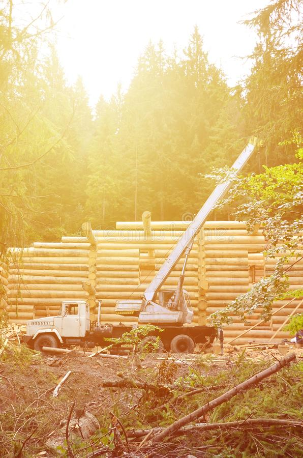 The process of building a wooden house from wooden beams of cylindrical shape. Crane in working condition stock photography