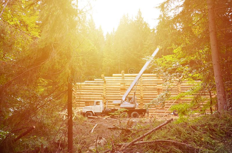 The process of building a wooden house from wooden beams of cylindrical shape. Crane in working condition stock photos