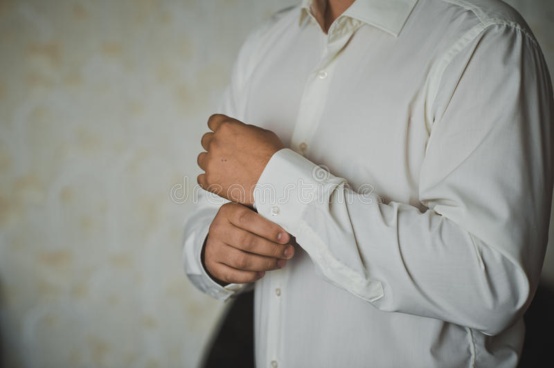 Process of clothing of cuff links. Hands of the young man clasping cuff links on shirt cuffs royalty free stock image