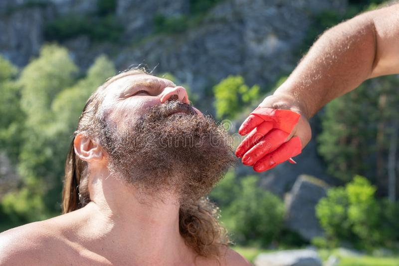 Process of coloring the male beard and hair on head. dyed hair and beard black at in open air. doing styling of beard. The process of coloring the male beard and stock photos