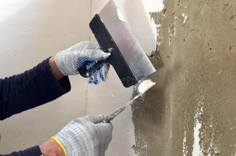 The process of the concrete wall putty two spatulas stock image