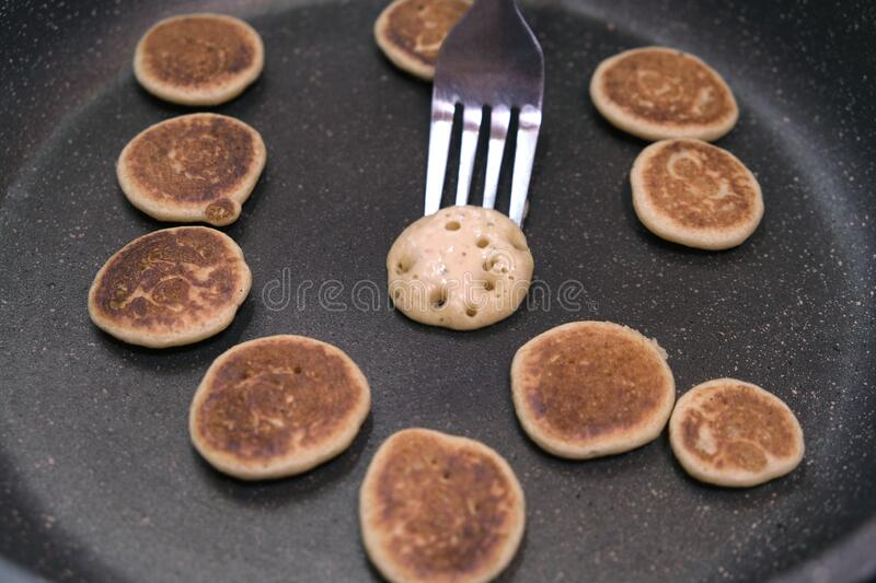 Process of cooking baked tiny pancake cereal - trendy quarantine food. Use fork to flip mini pancakes to other side on hot pan. royalty free stock image