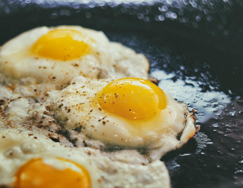 Process of cooking fried eggs. Vintage photo look. Vintage photo of Fried eggs in a frying pan. Process of cooking eggs closeup. Food Background royalty free stock photo