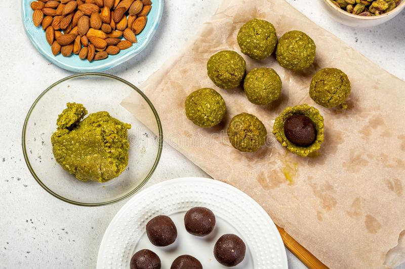 The process of cooking raw vegan marzipan sweets. Chocolate praline balls wrapped in marzipan shell. Step of cooking marzipan paleo-candies. Healthy eating stock photo