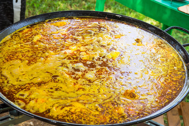 Process of cooking Spanish paella or jambalaya in large flat frying pan. Ingredients meat, rice, vegetables, simmering in broth royalty free stock photo