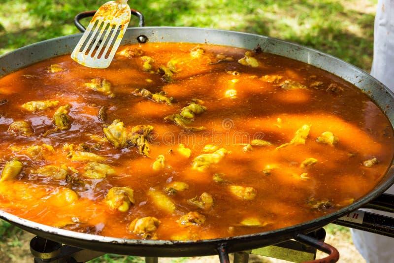 Process of cooking Spanish paella or jambalaya in large flat frying pan. Metal turner tossing ingredients in tomato sauce stock photo