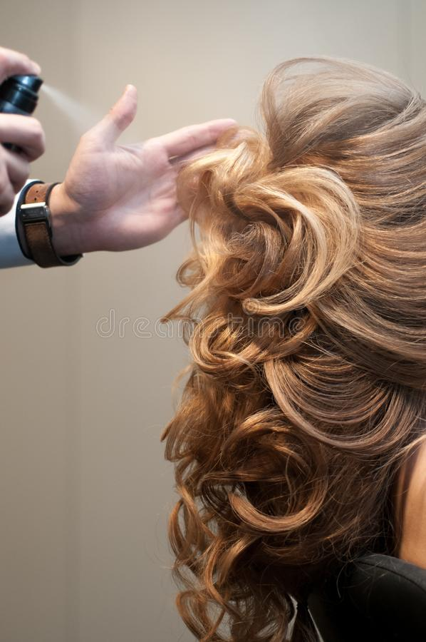 Process of creating evening hairstyles for a girl with long blond hair by a master hairdresser stock photo