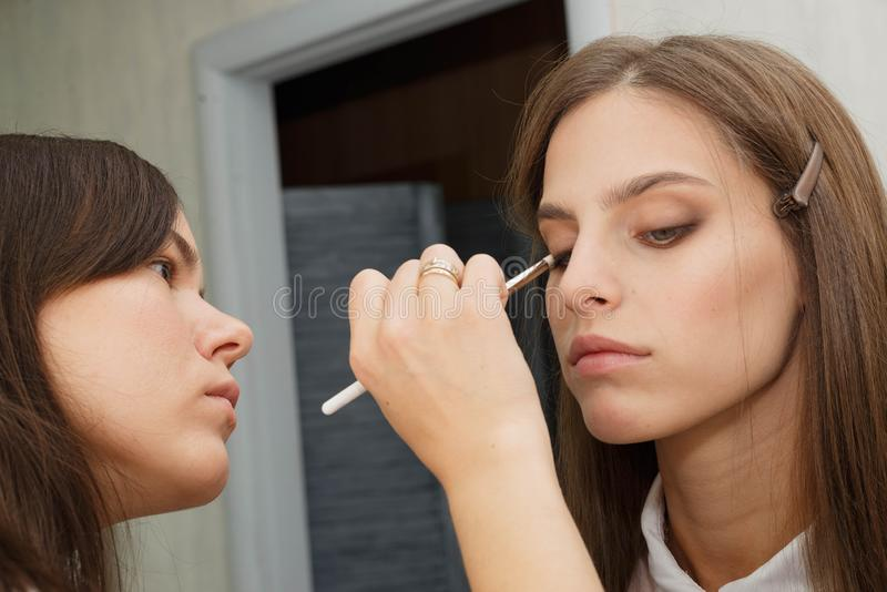 The process of creating makeup. Makeup artist working with a brush on the face of the model royalty free stock image