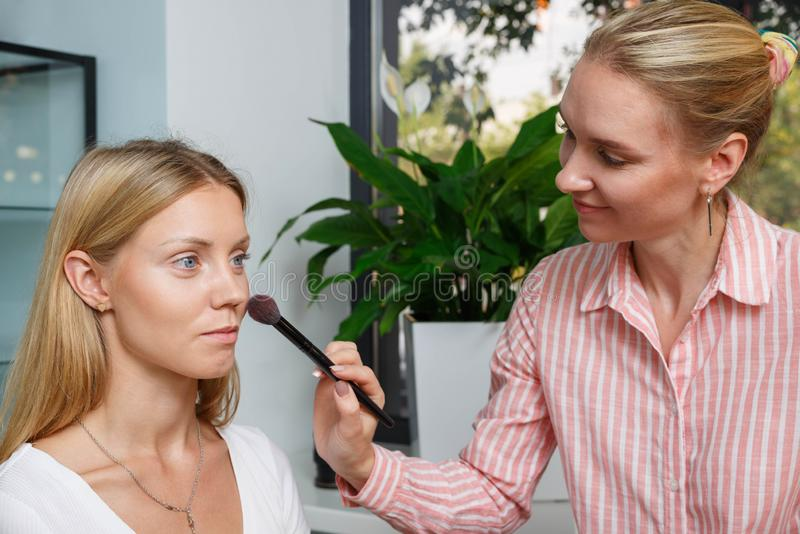 The process of creating makeup. Makeup artist working with a brush on the face of the model royalty free stock photos