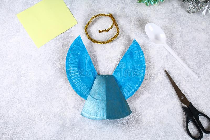 The process of creating your own Christmas angel from a disposable cardboard plate, a plastic spoon and paper. Christmas decor. stock photography