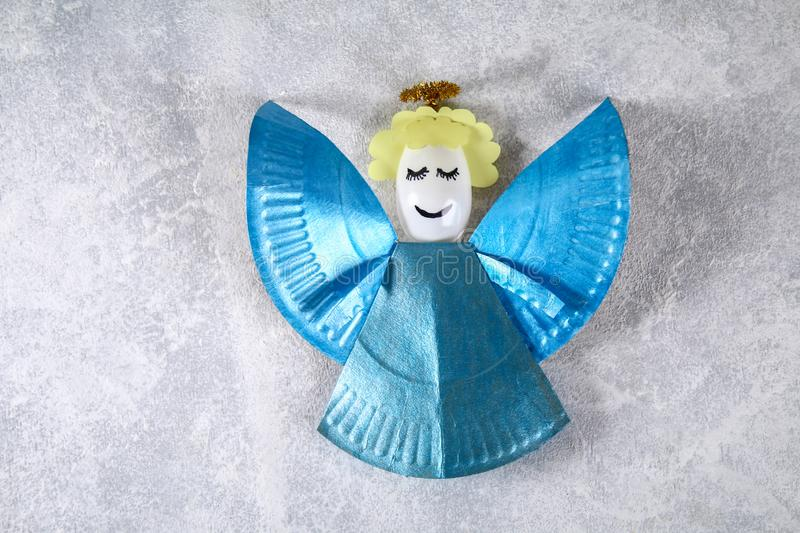 The process of creating your own Christmas angel from a disposable cardboard plate, a plastic spoon and paper. Christmas decor. stock images