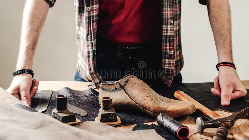 Process of creation custom made shoes. Hands of cobbler dealing with cobbler tool, close up. Workplace of shoe designer. Small stock image