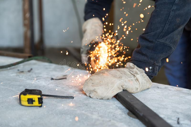 Process of cutting metal profile with electric angle grinder. Preparation of parts for welding of metal construction. People at wo royalty free stock photography