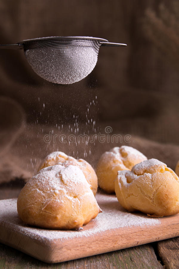 Process of decorating with icing sugar profiteroles. Rustic style. Process of decorating with icing sugar profiteroles. Rustic royalty free stock photography