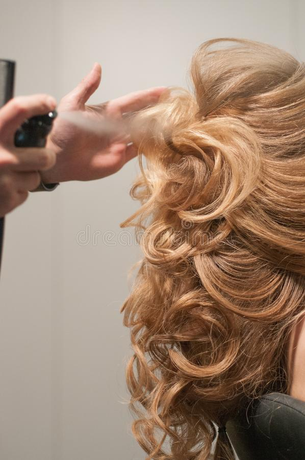 Process of evening creating hairstyles for a girl with long blond hair by a master hairdresser stock photos
