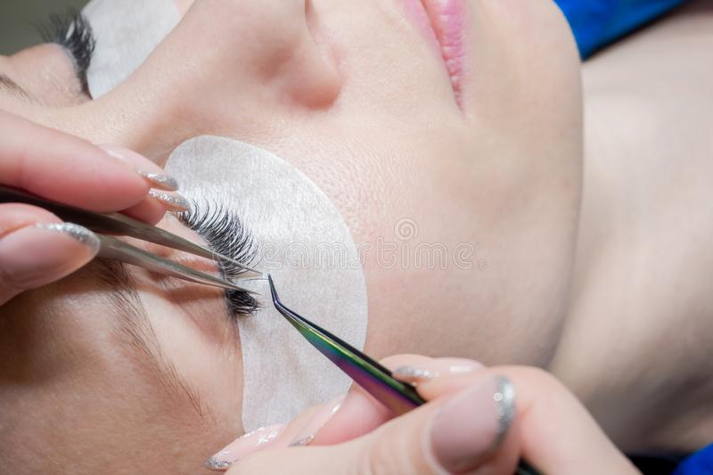 Process of eyelash extension in a beauty salon. Close up royalty free stock photography