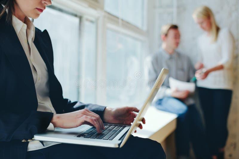 Process för kontorsarbete Kvinna med bärbar dator- och lagmöte i vind royaltyfri fotografi