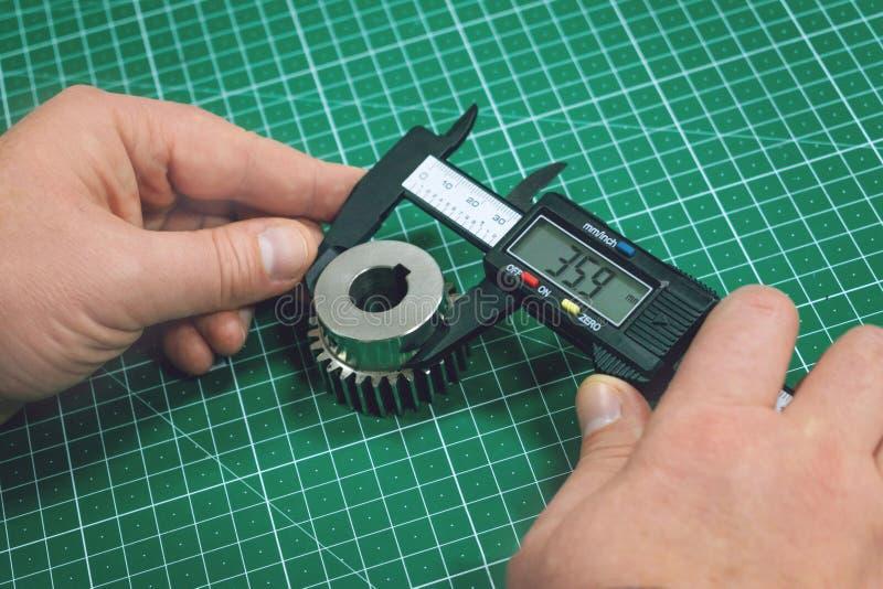 Process för metallkugghjulmätning Fabriksman, arbetare som mäter på ståldetaljen, kugghjul med digitala Vernier Caliper på semina royaltyfri foto