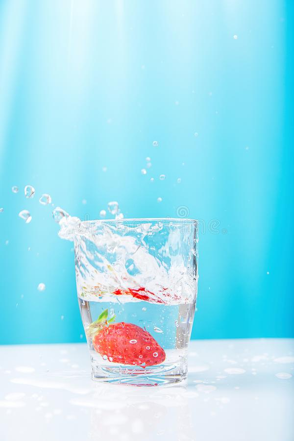 Process of Falling of Ripe Juicy Floating Strawberry into Glass of Fresh Clear Water. Beautiful High Splashes Drops. Bright Blue Background Sunlight. Summer stock photo