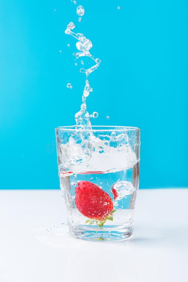 Process of falling of ripe juicy strawberry into glass of fresh pure water with splashes bubbles blue white background. Hydration stock photography