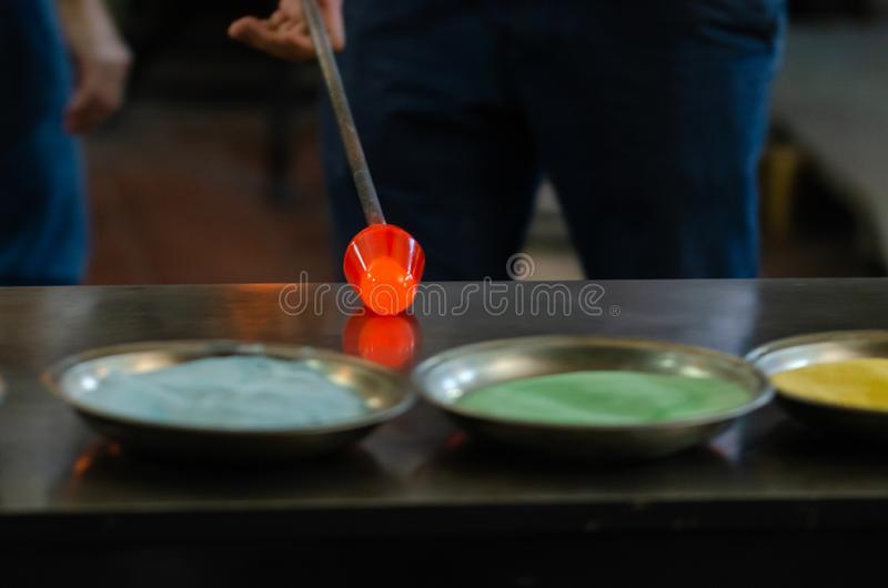 The process of glass object making. He is shaping the molten glass.Manufacturing glass object in a traditional oven in workshop stock photos