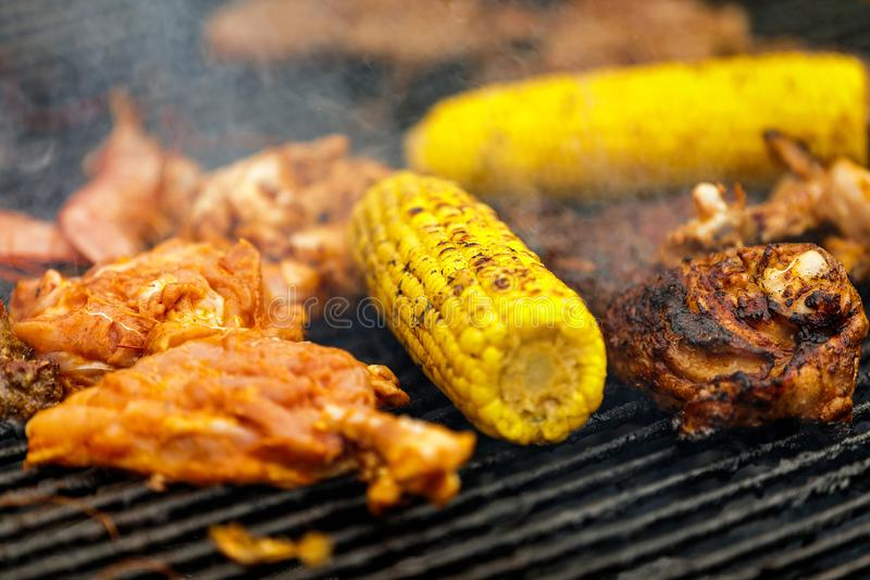 Grilling corn cobs, chicken legs and shrimp. Process of grilling corn cobs, chicken legs and shrimp stock photo