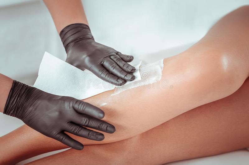 Master being concentrated on removing unwanted hair on the legs. Process of hair depilation. Master being concentrated on removing unwanted hair on the legs of royalty free stock images