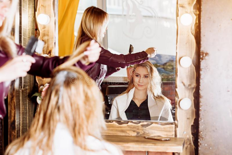 The process of hair treatment, hair colouring. Hairdresser is dying female hair. Beautiful attractive client sitting before at stock photos