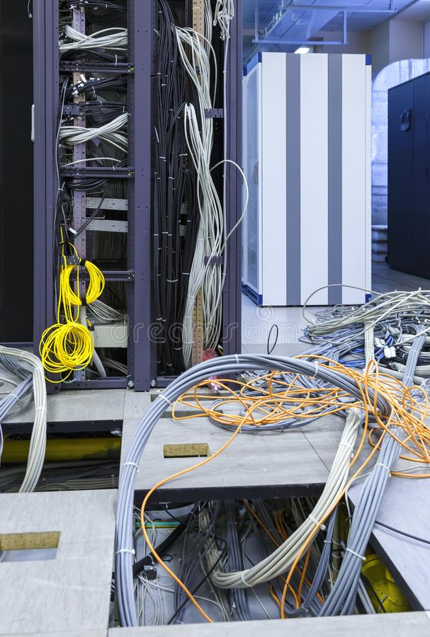 Process of installation and cabling in modern data center. Server rack with skeins of cables next to the disassembled stock image