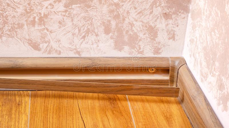 Process installing baseboard,mounting and assembly plinth close-up.  stock photo