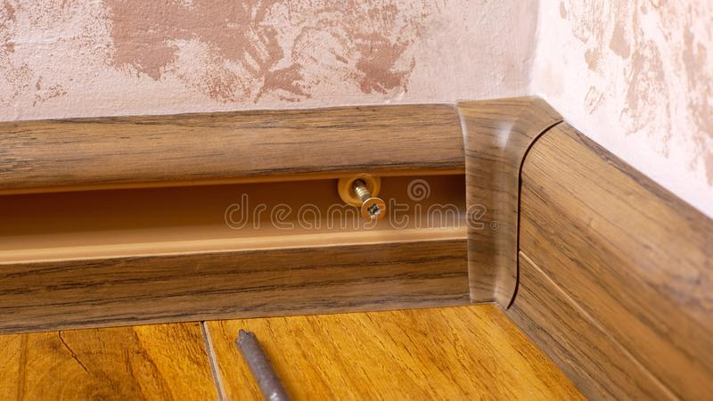 Process installing baseboard,mounting and assembly plinth closeup.  stock photography