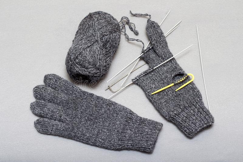 The process of knitting woolen gloves on knitting needles royalty free stock photos