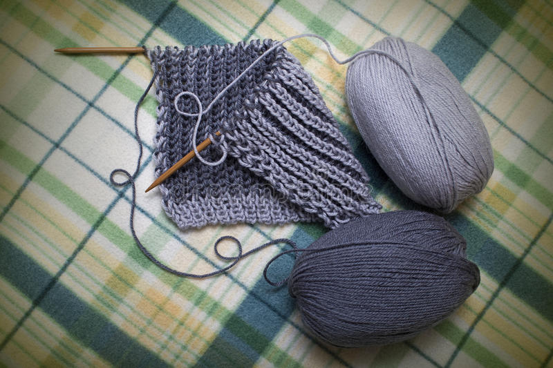 Process of knitting yarn scarf gray two-tone royalty free stock photos