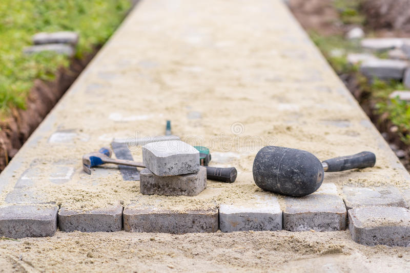 Process of laying pavement at yard. Stones are laying on sand. Work tools. stock image