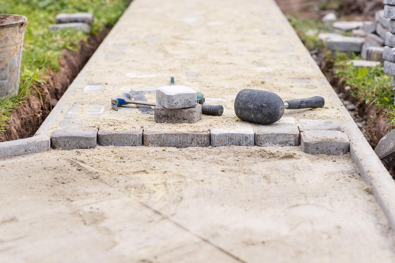 Process of laying pavement at yard. Stones are laying on sand. Work tools. royalty free stock images
