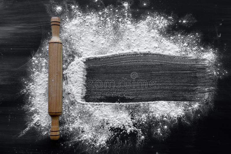 The process of making baking at home, flour and rolling pin are on a dark background stock photography