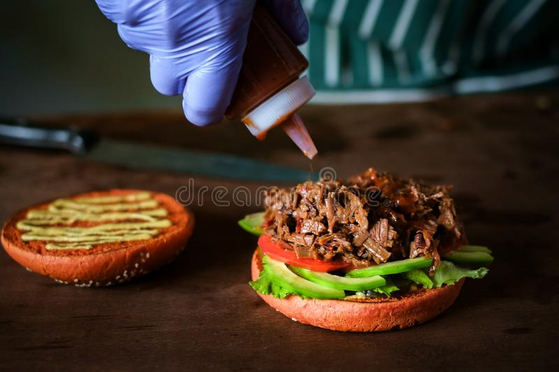Process of making burger. chef hands in gloves cooking beef burger. Process of making burger. chef hands in gloves cooking beefburger with avocado and tomato stock photos