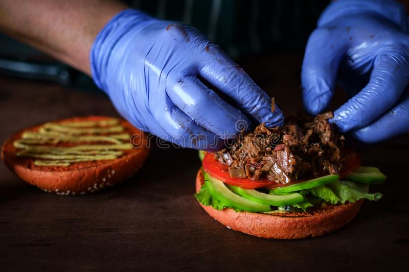 Process of making burger. chef hands in gloves cooking beefburger with avocado. And tomato royalty free stock image