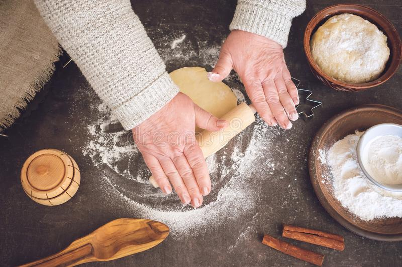 Process of making christmas cookies. Mature woman, granny hands making dough. Ingredients for baking pie: flour, pastry, crockery, kitchen utensils, fir tree royalty free stock photo