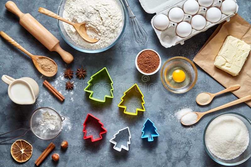 The process of making gingerbread cookies. Baking ingredients for homemade pastry on dark background. Top view, flat lay royalty free stock photography